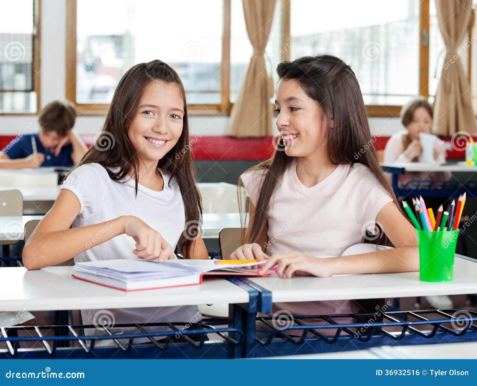 Happy Schoolgirl Sitting With Friend At Desk