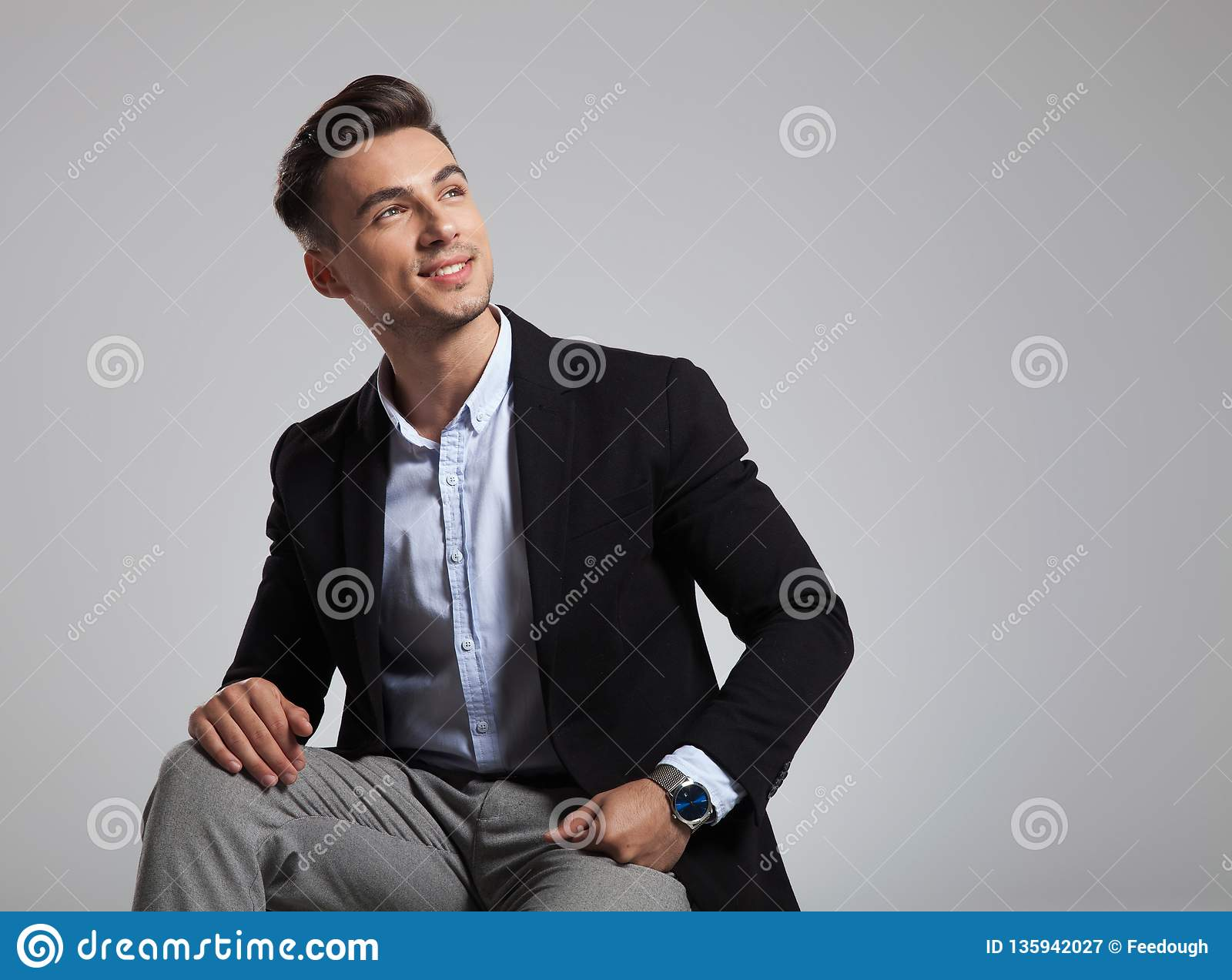 Happy seated businessman in black suit looks up to side