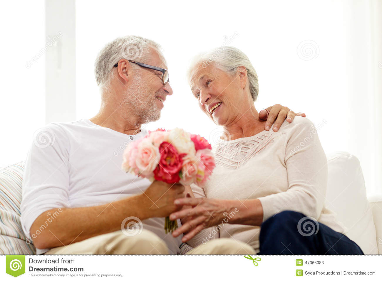 Happy senior couple with bunch of flowers at home