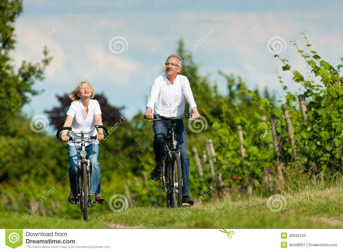 Happy Senior Couple Cycling Outdoors In Summer Stock