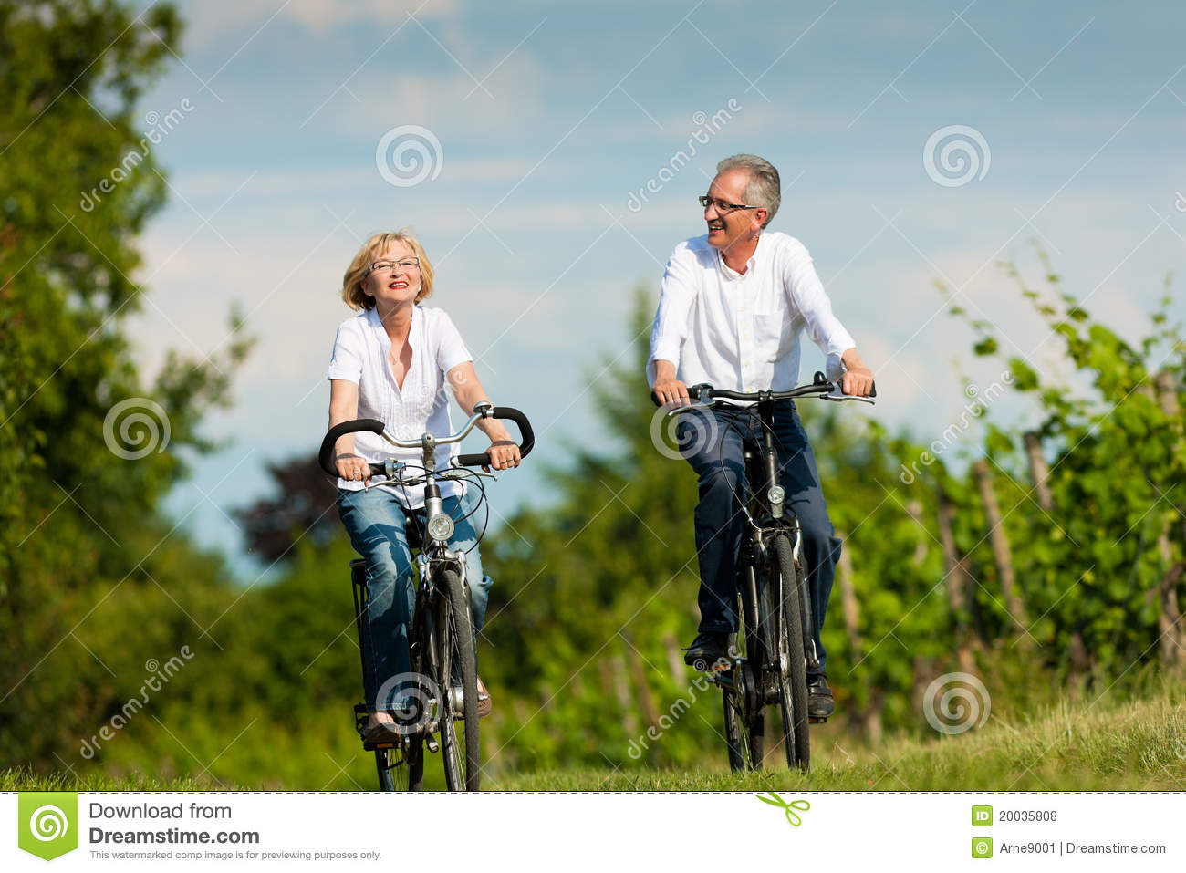 Happy Senior Couple Cycling Outdoors In Summer Stock Photo