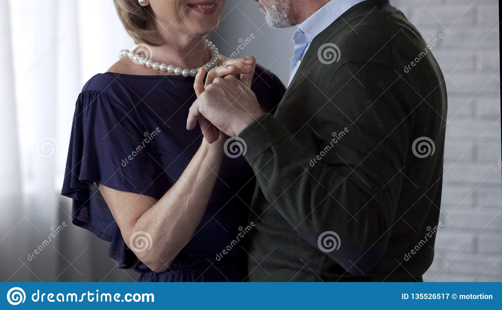 Happy senior couple dancing, looking at each other and smiling, anniversary