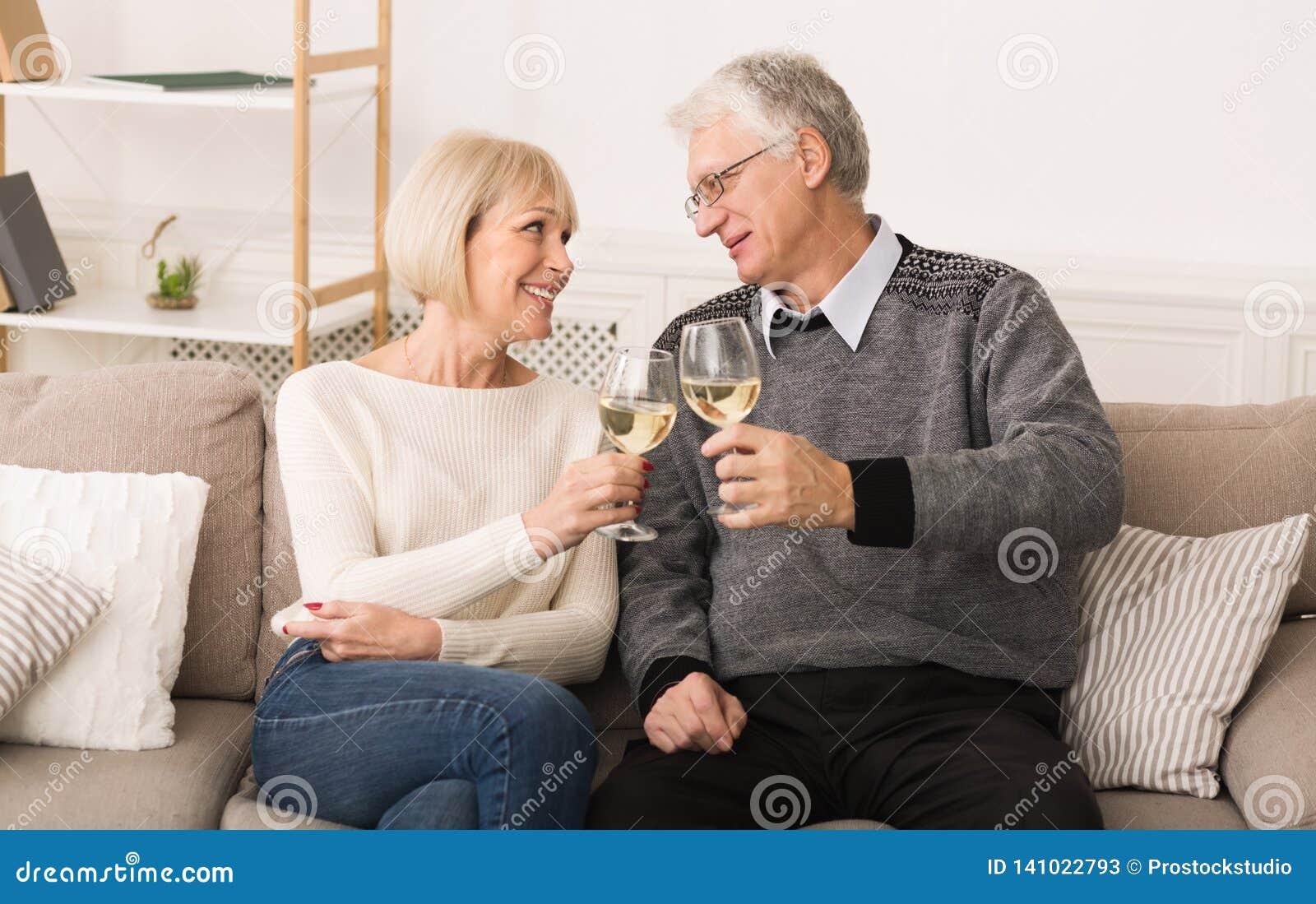 Happy senior couple drinking wine, celebrating wedding anniversary