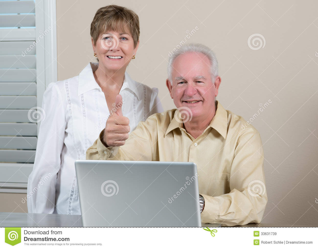 Happy senior couple with laptop giving thumbs up