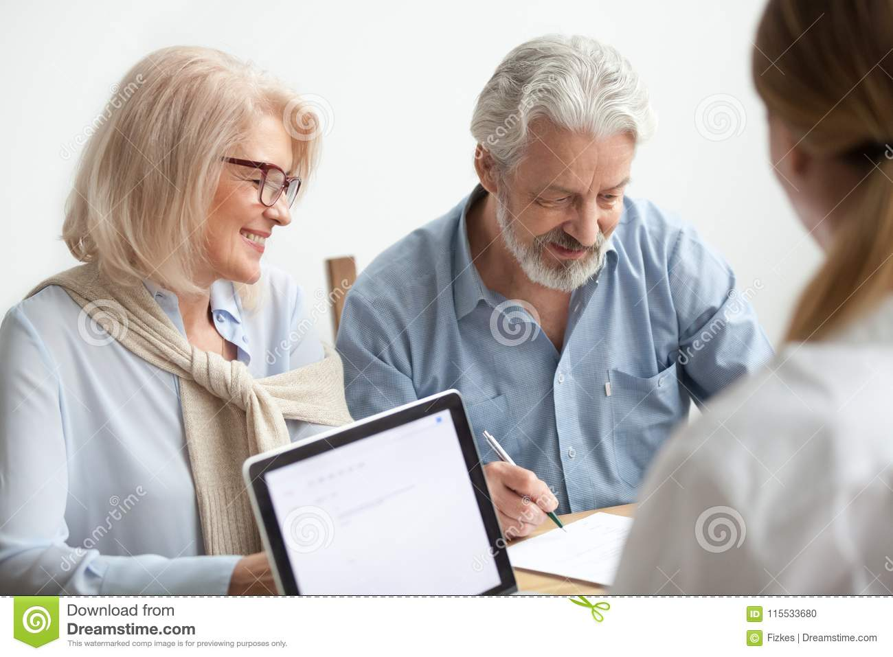 Happy senior couple signing document at meeting with financial a
