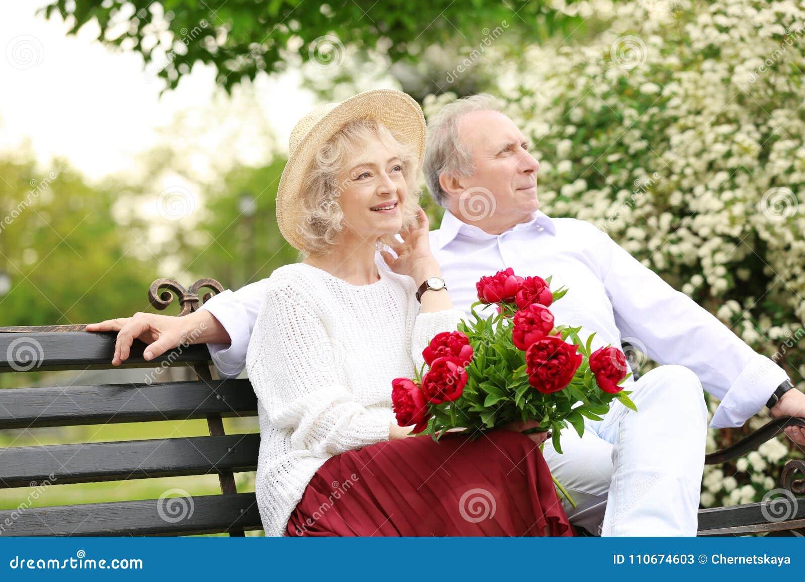 Happy senior couple sitting on bench