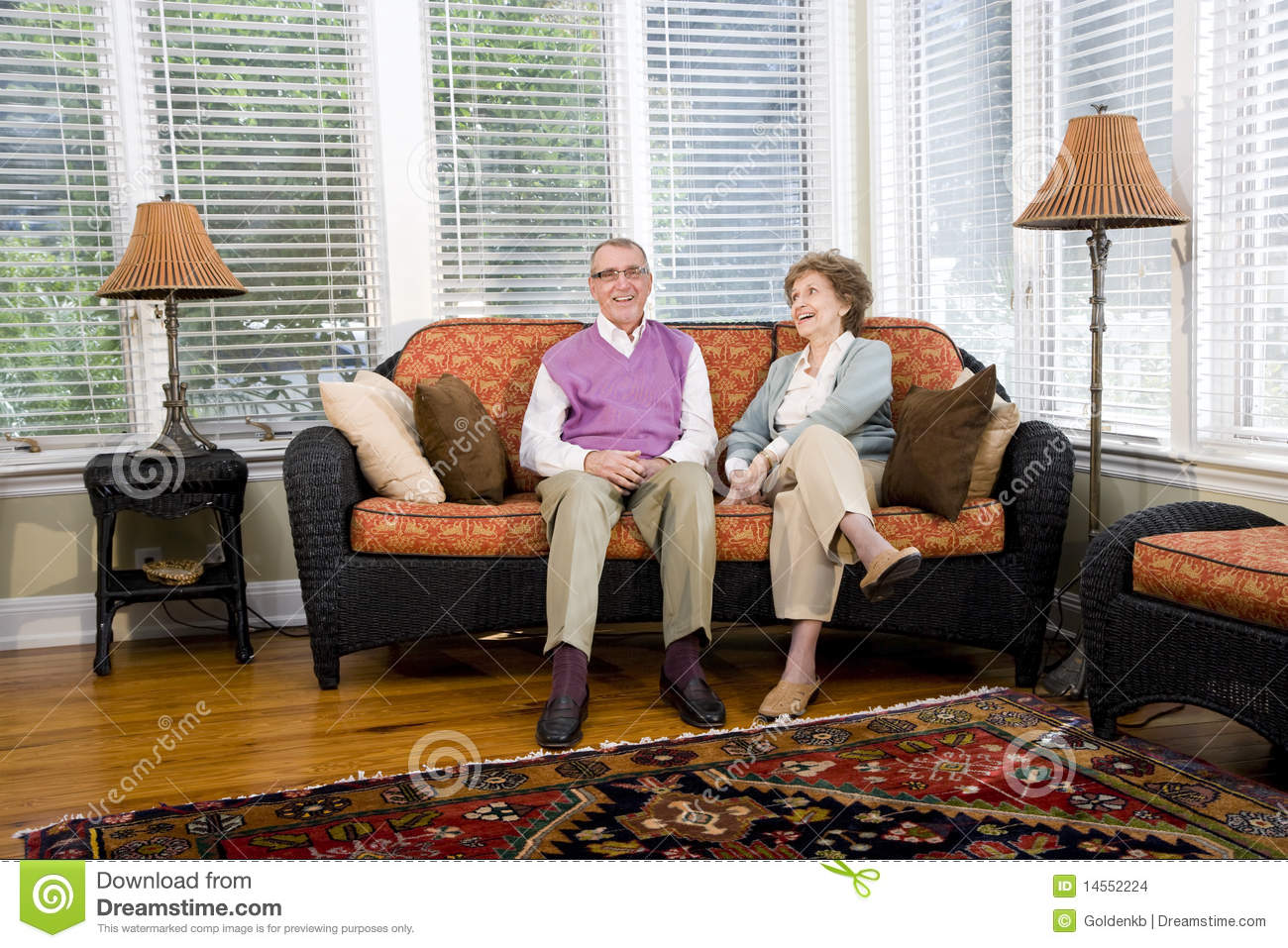 Happy senior couple sitting on living room couch stock for Sitting furniture living room