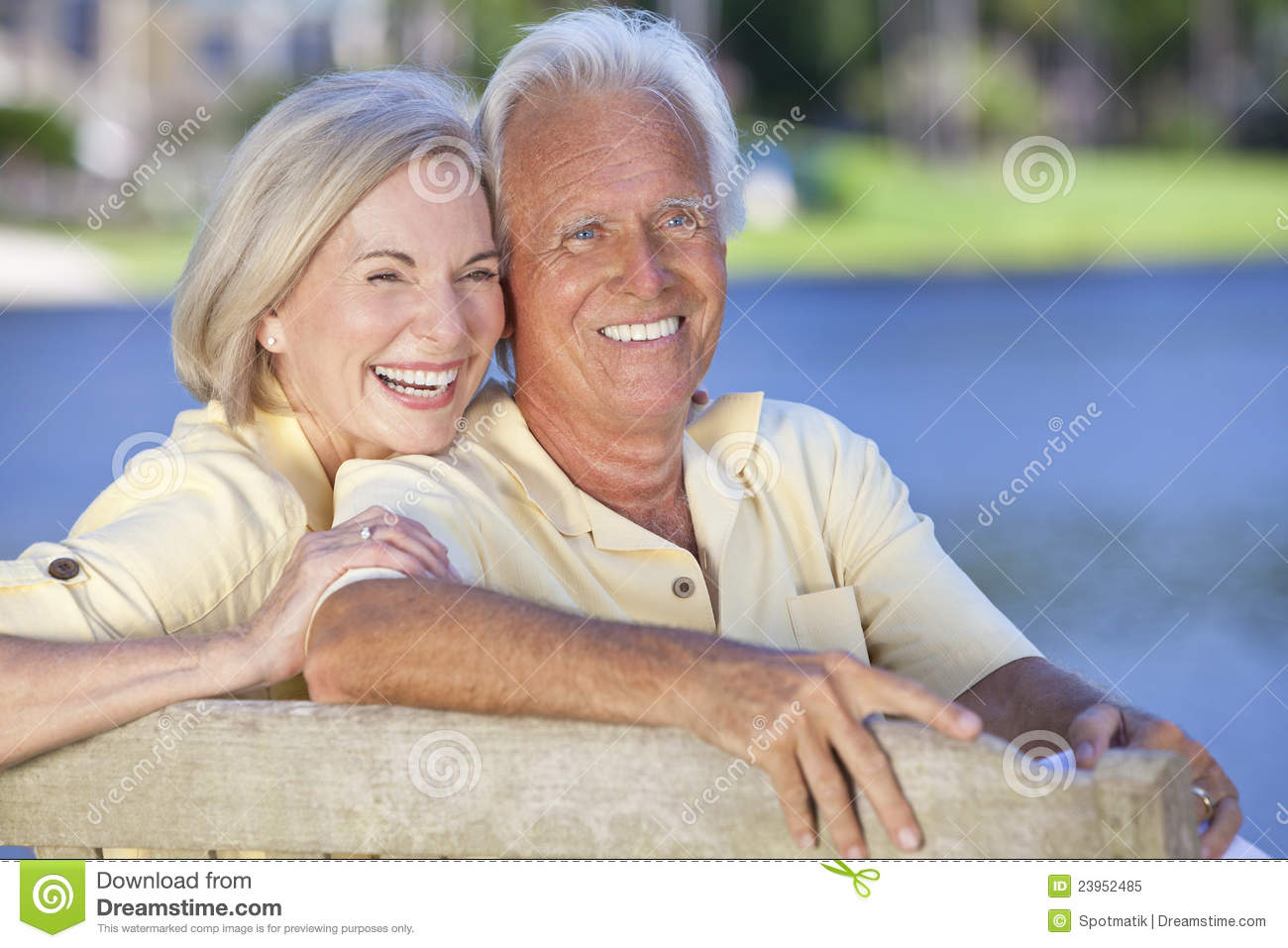 Happy Senior Couple Sitting On Park Bench Laughing