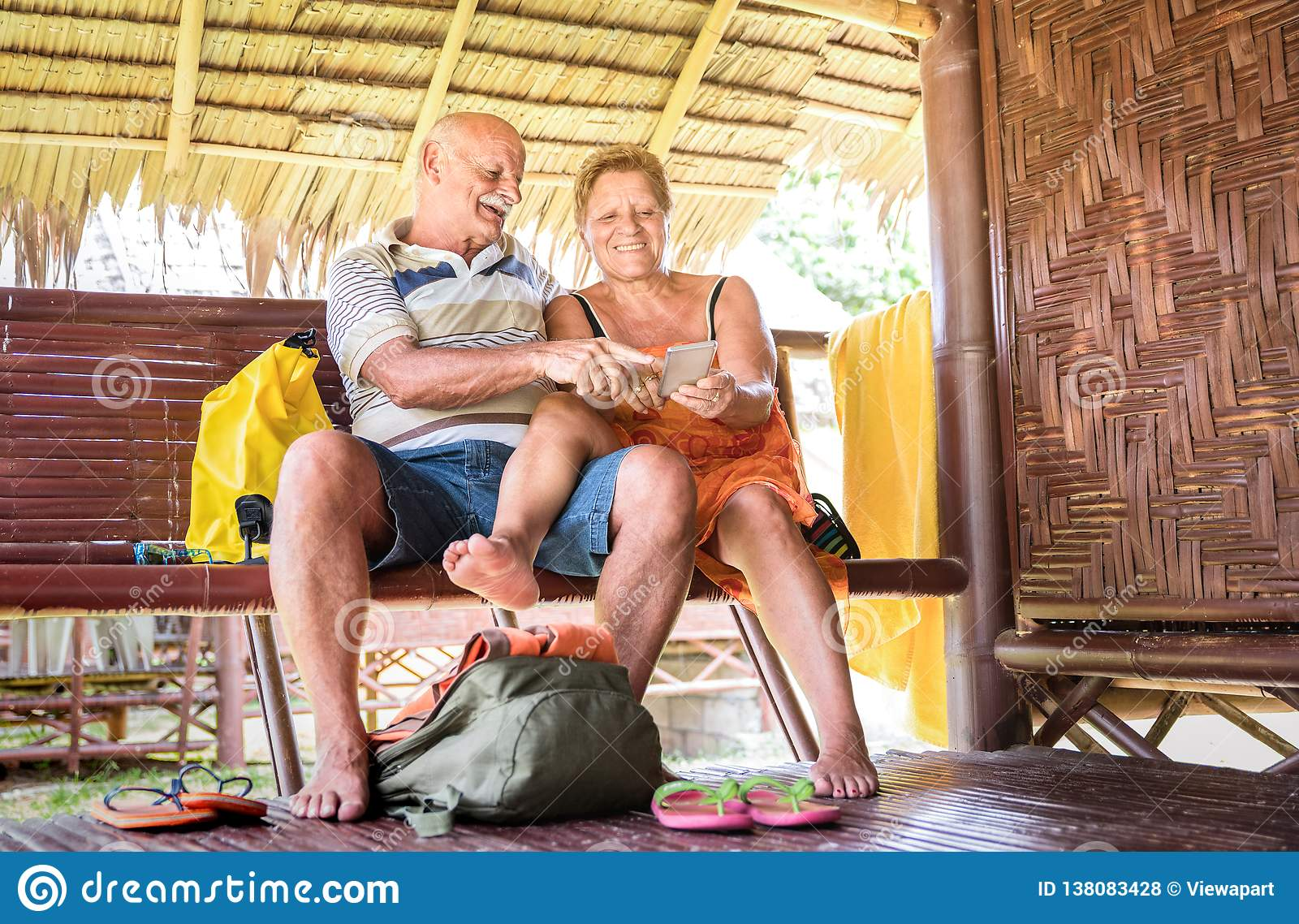 Happy senior couple using mobile smart phone at bungalow luxury resort - Active elderly and travel concept always connected