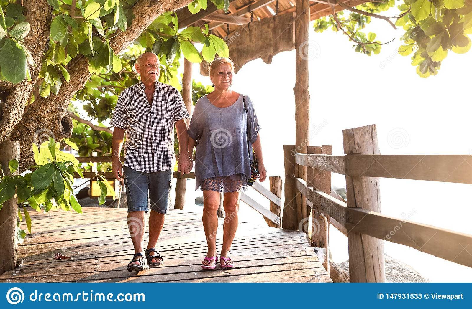 Happy senior couple walking holding hand at Koh Phangan beach promenade - Active elderly and travel lifestyle concept