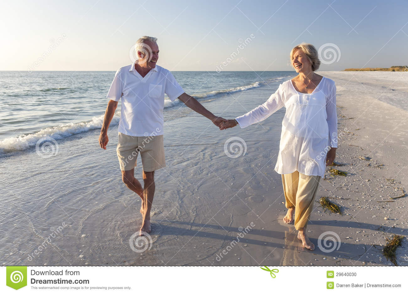 54c00631f6a4 Happy senior men and women couple walking and holding hands on a deserted  tropical beach with bright clear blue sky