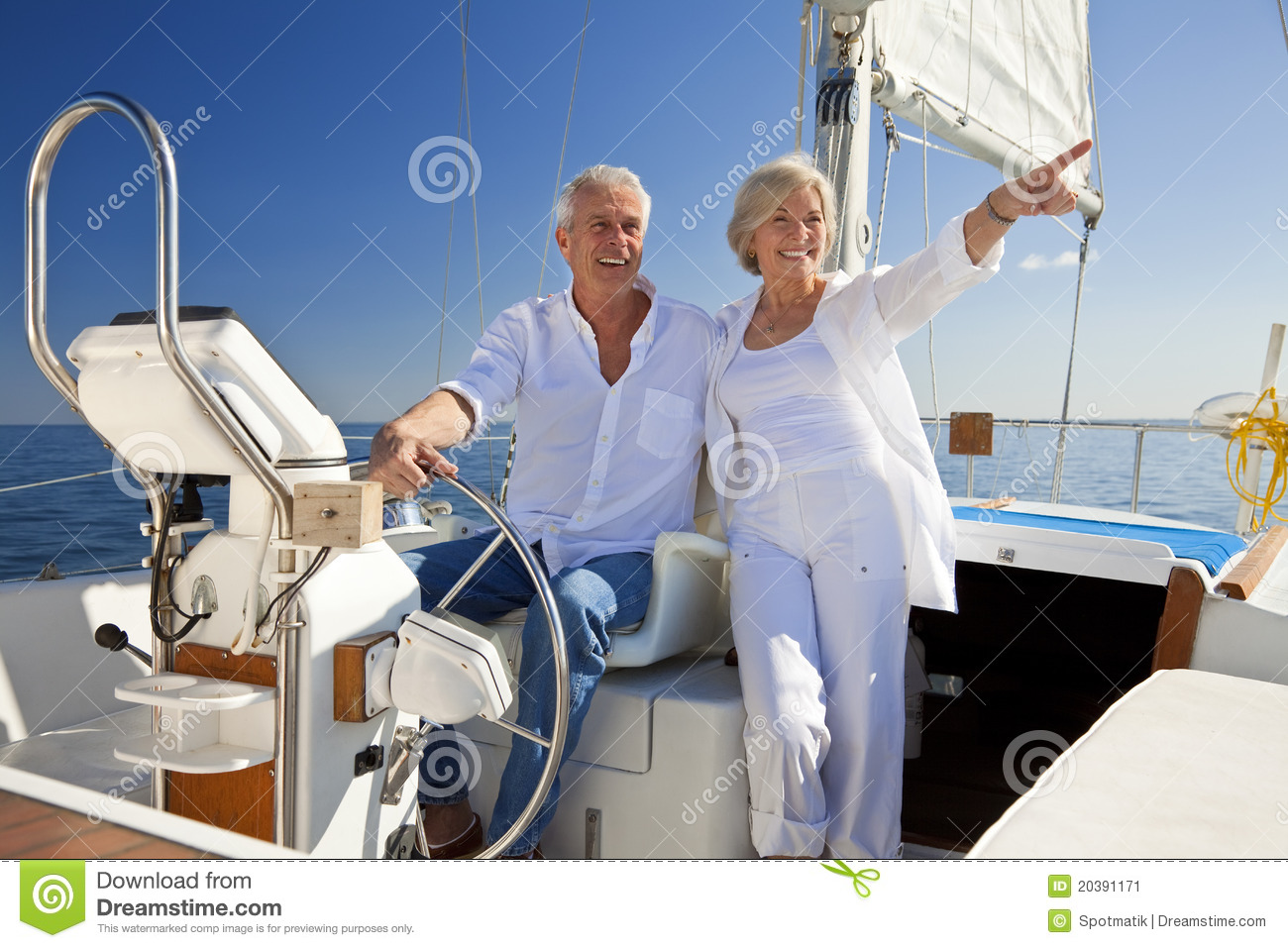 Happy Senior Couple At The Wheel of a Sail Boat