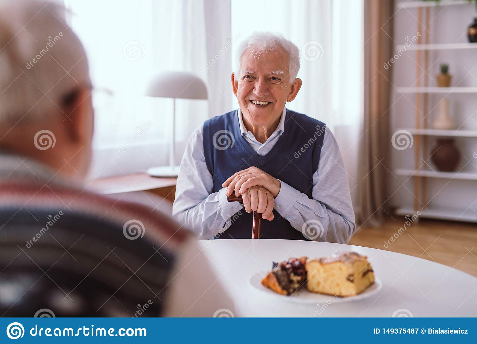 Happy senior man laughing with his old friend over the piece of cake