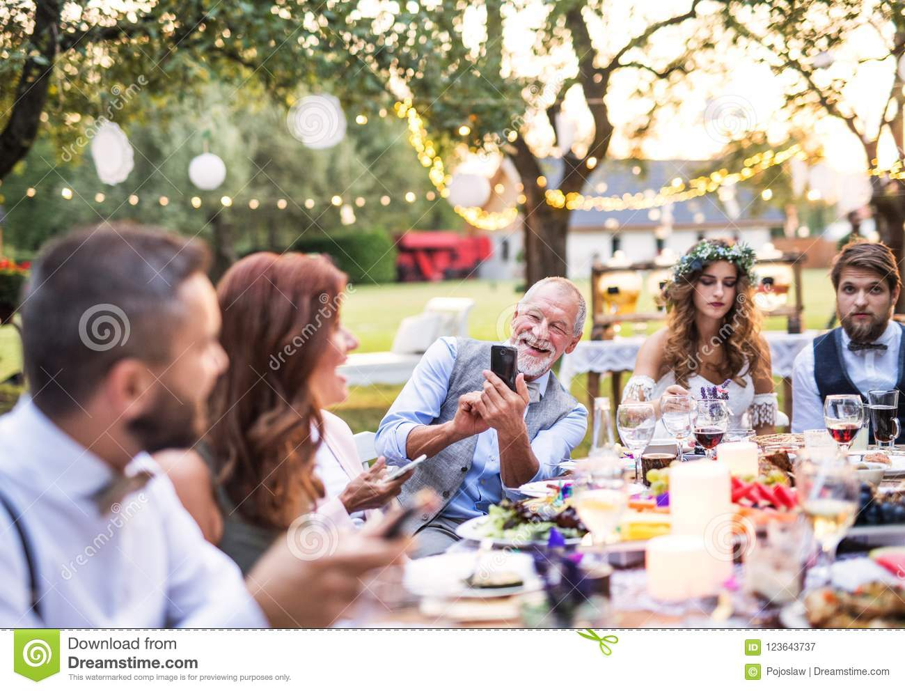 A senior man taking selfie at the wedding reception outside in the backyard.