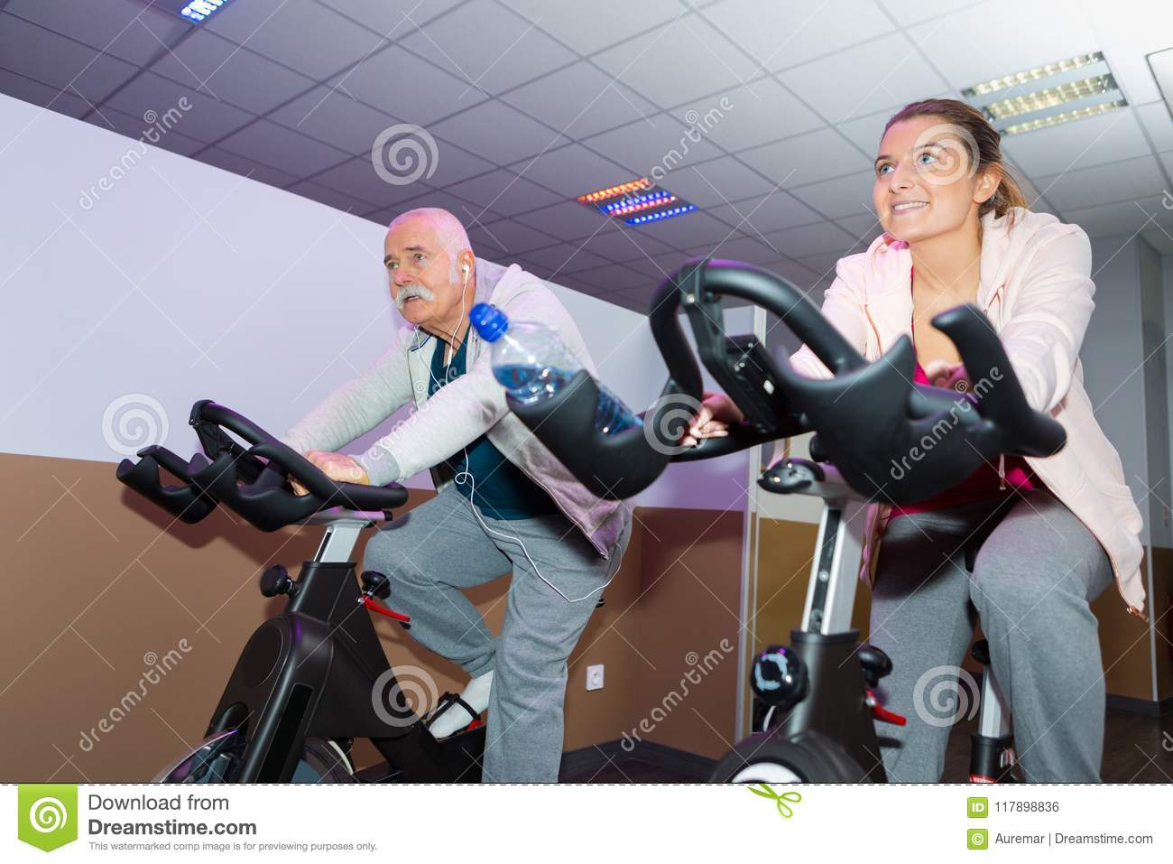 Happy senior people group exercising in spinning class in gym