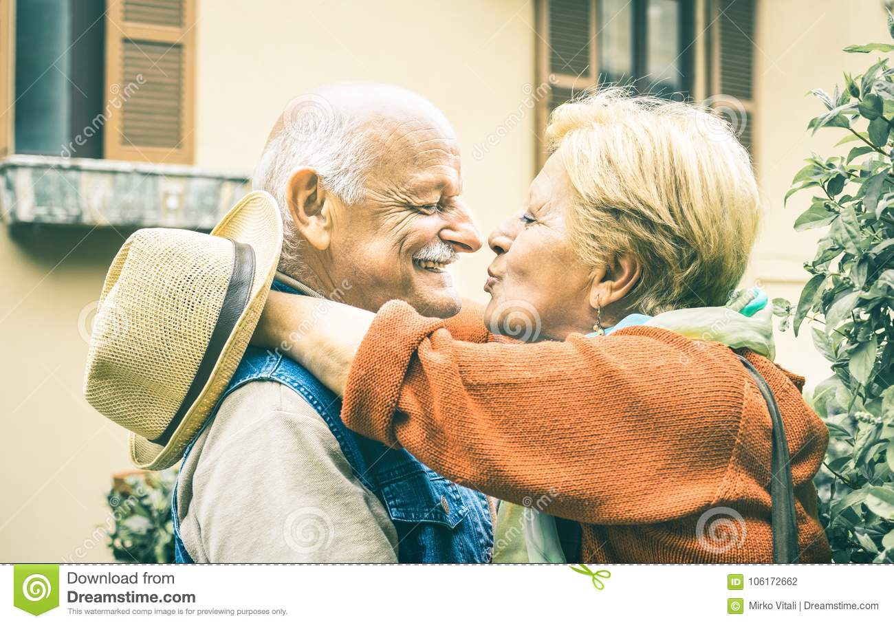 Happy senior retired couple having fun kissing outdoors at travel time
