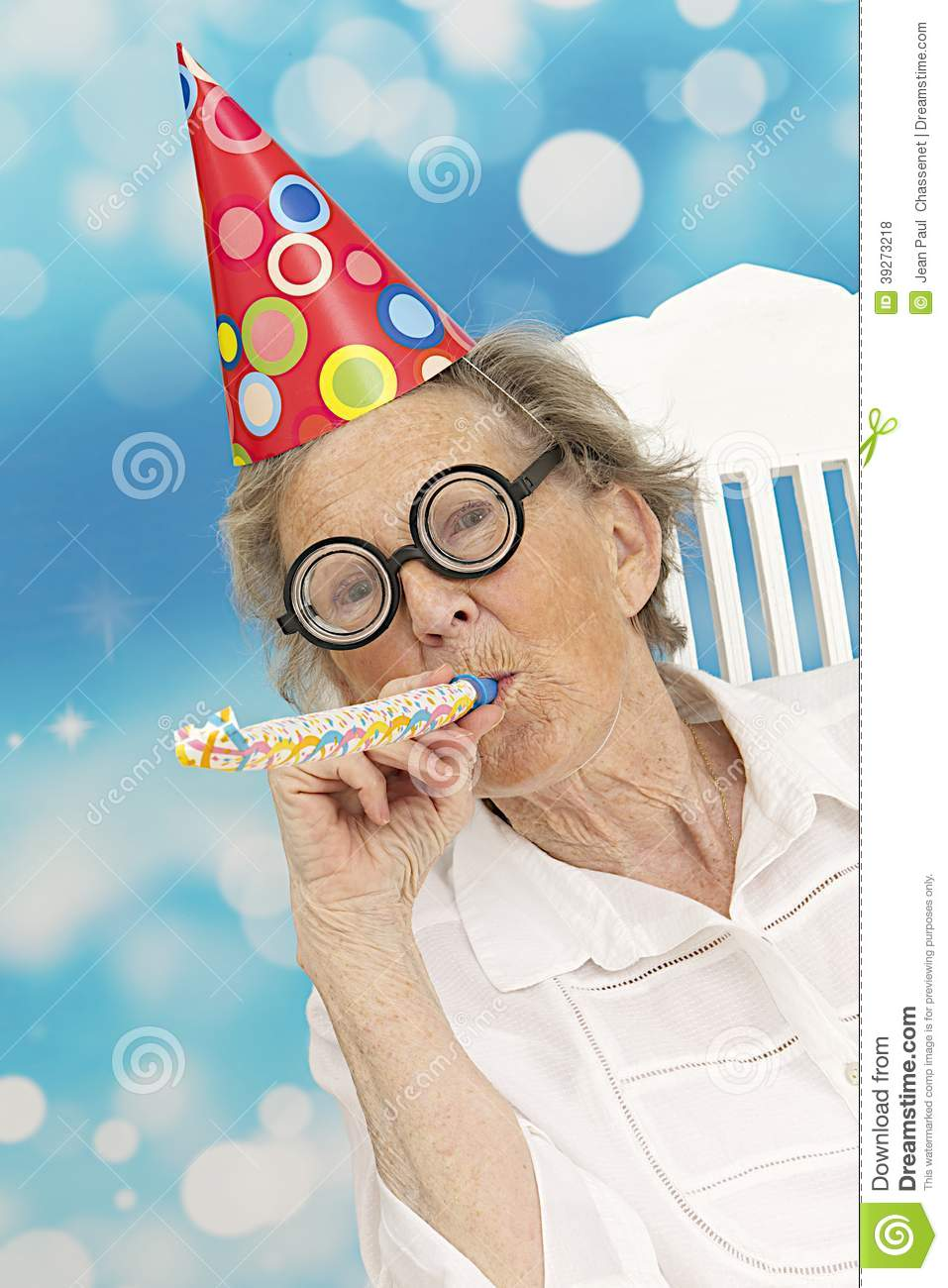 Happy senior woman with funny glasses a party hat and a noise maker