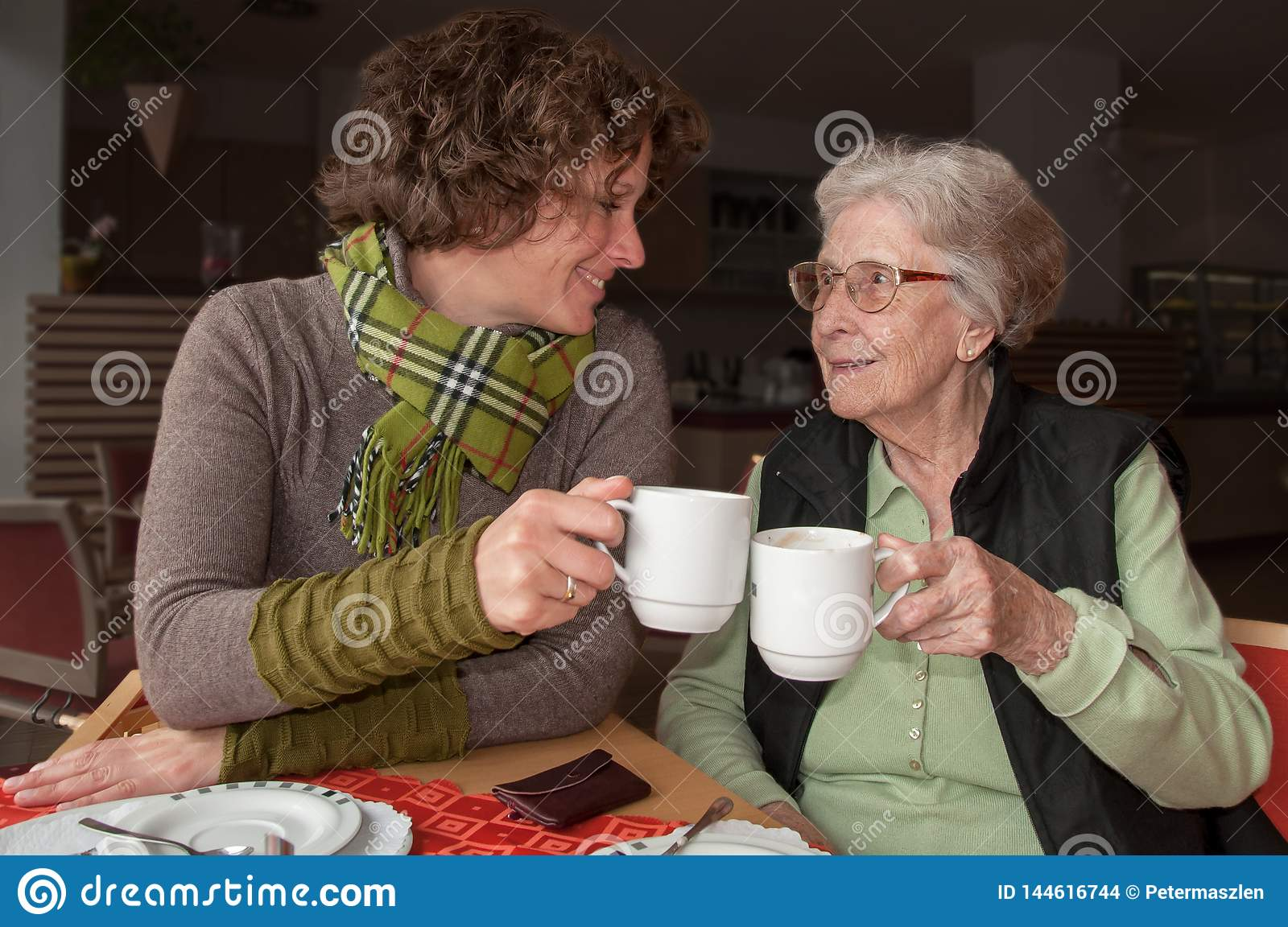 Happy senior woman and granddaughter drinking coffee