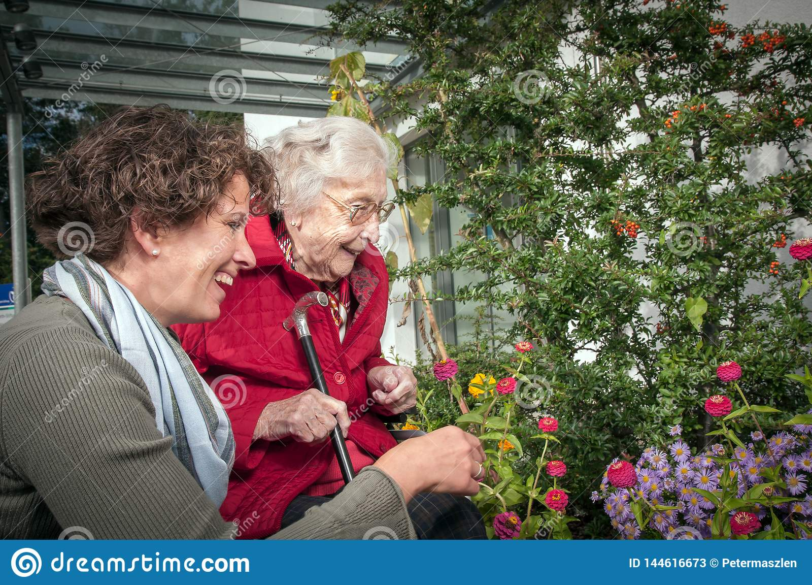 Happy senior woman and granddaughter having fun in the garden
