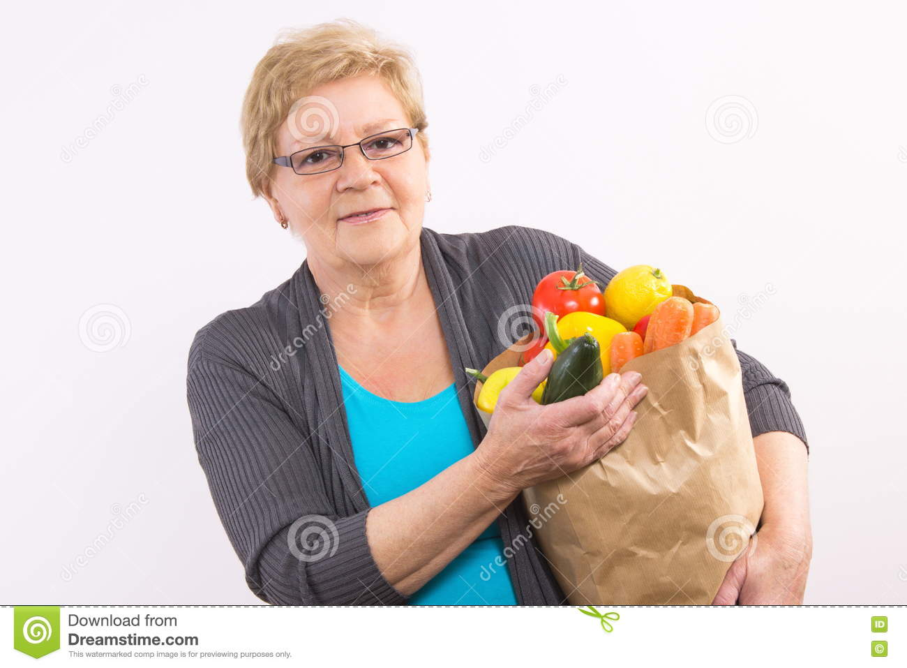 Happy senior woman holding shopping bag with fruits and vegetables, healthy nutrition in old age