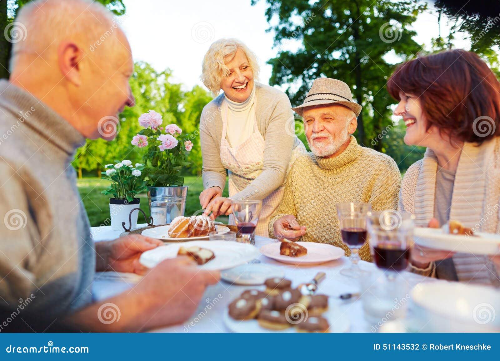 happy seniors at birthday party with cake stock photo