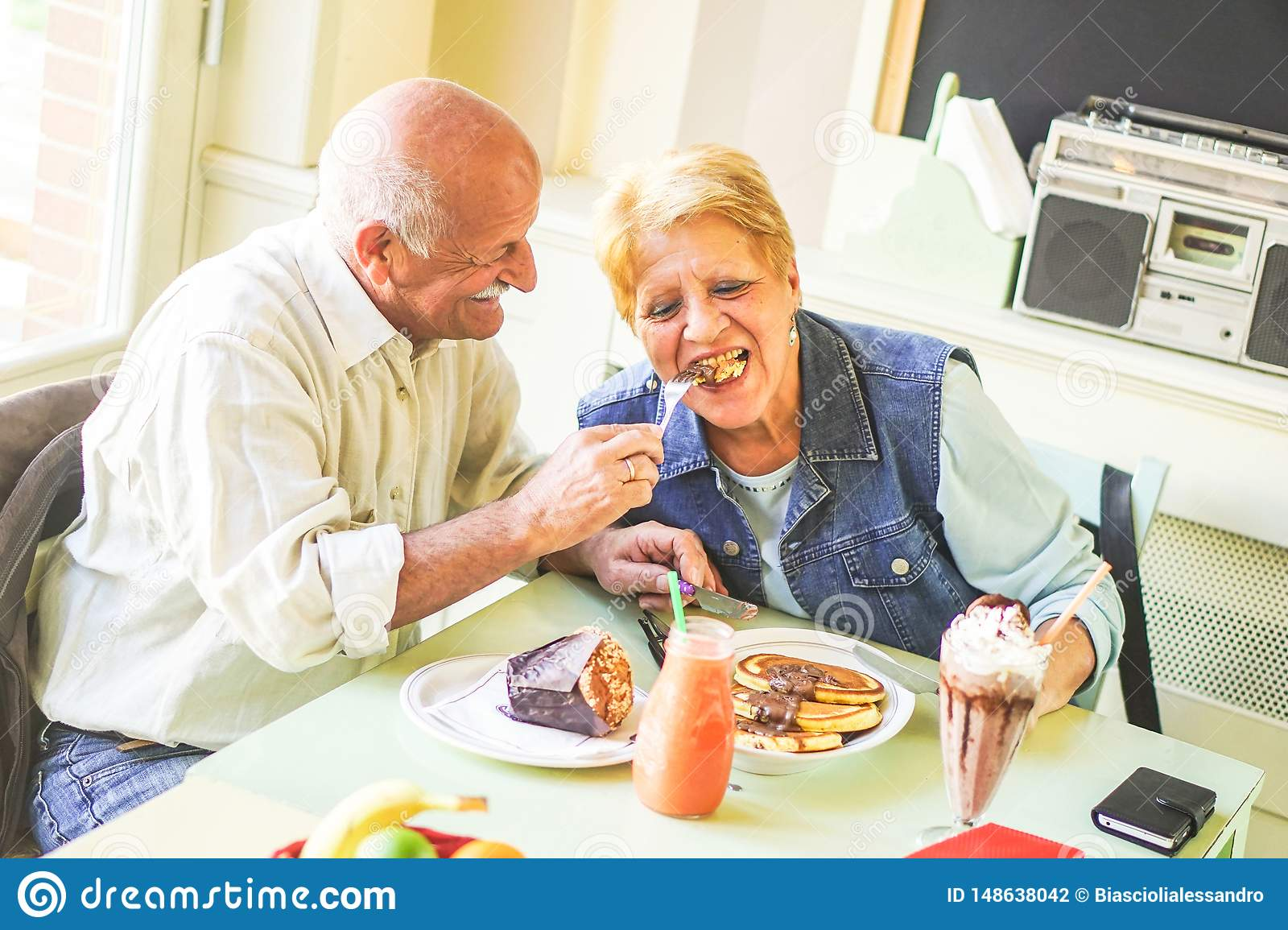 Happy seniors couple eating pancakes in a bar restaurant - Retired people having fun enjoying lunch together