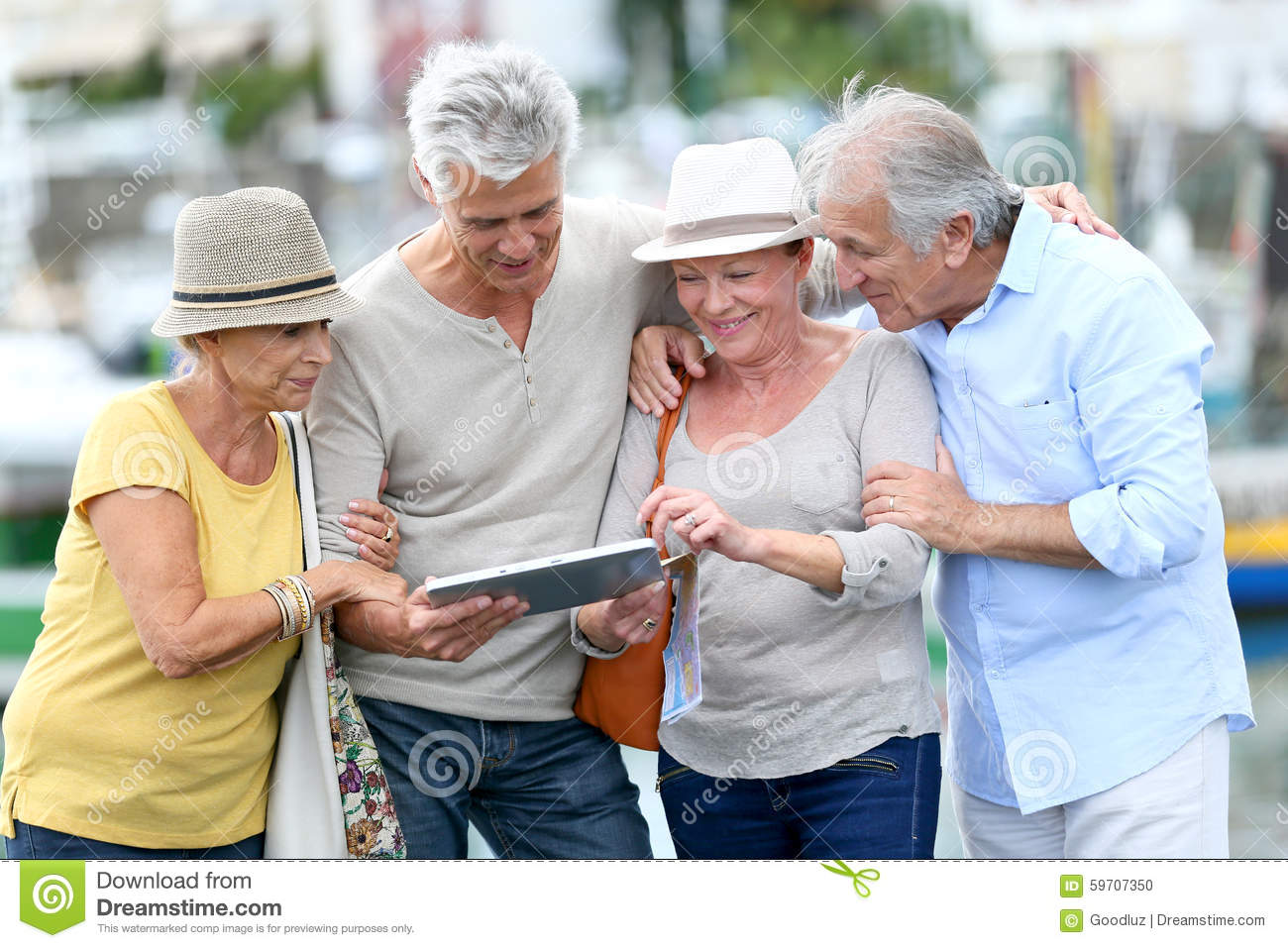 Happy seniors travelling and visiting using tablet