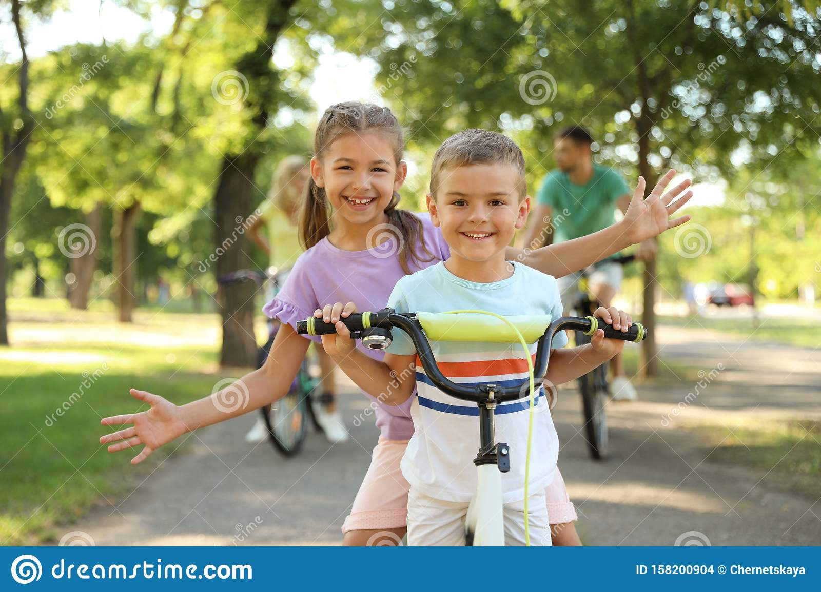Happy siblings and their riding bicycles in park