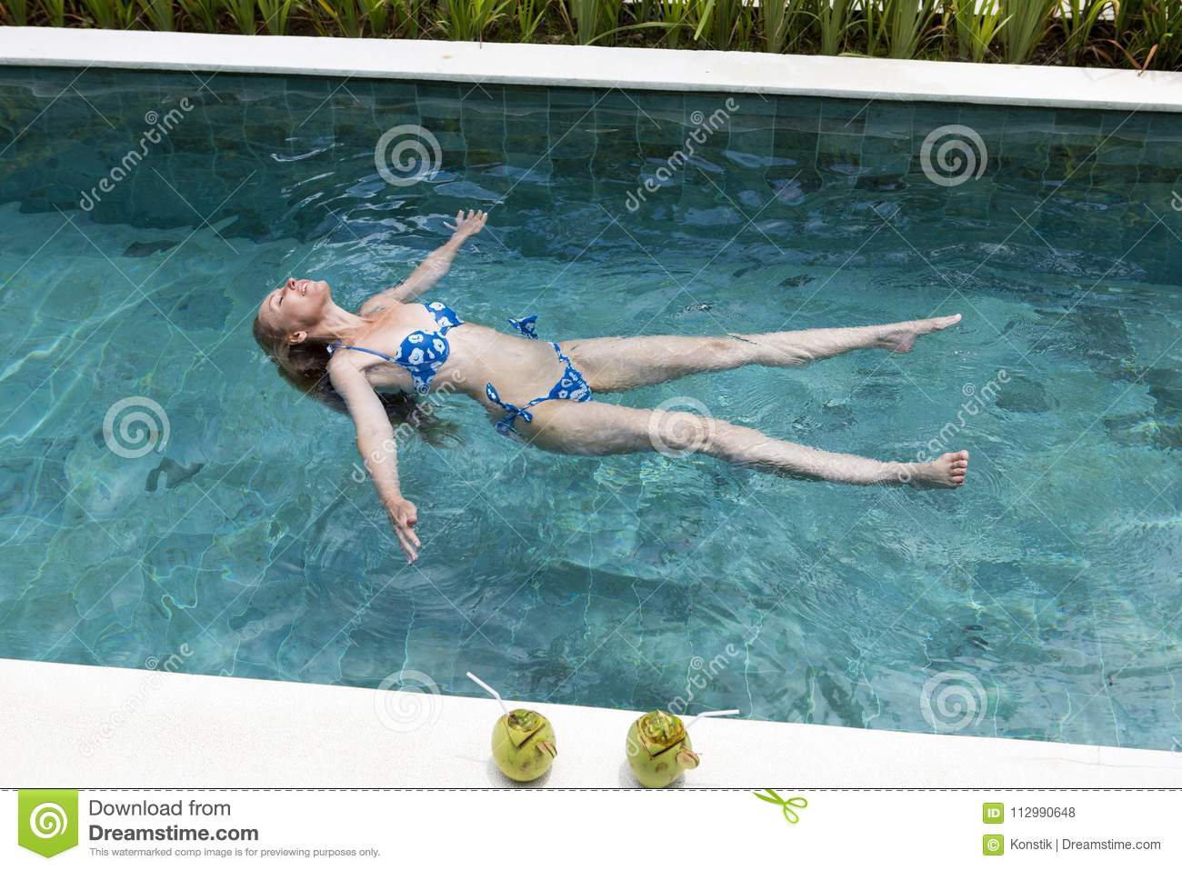 Happy slender young woman lies on a water surface in the pool and has a rest