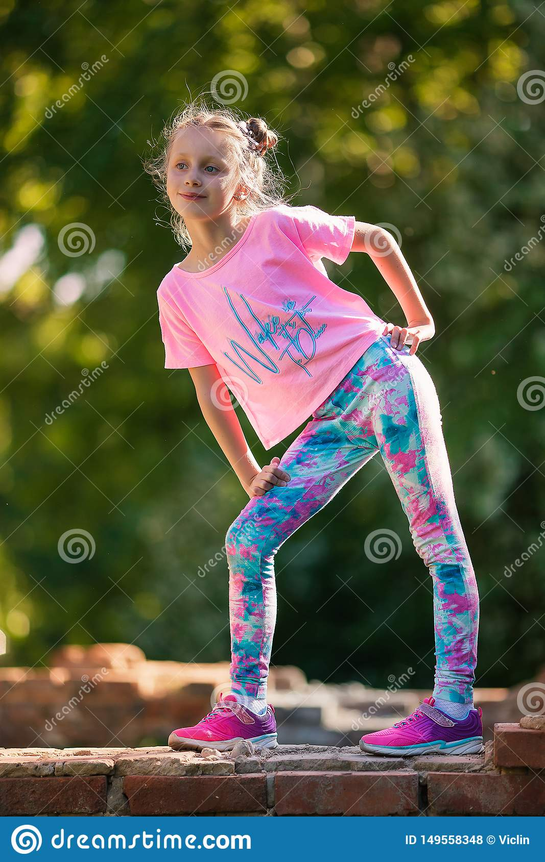 Happy small child jumping active for pleasure. Active and energetic girl having fun in summer. The concept of sports, dance, hip