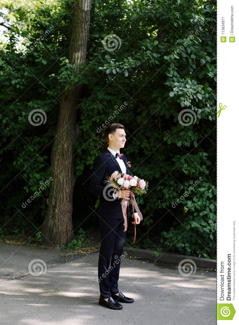 Happy smile bridegroom is waiting for the bride with amazing bouquet of flowers in classic suit with bow tie in green