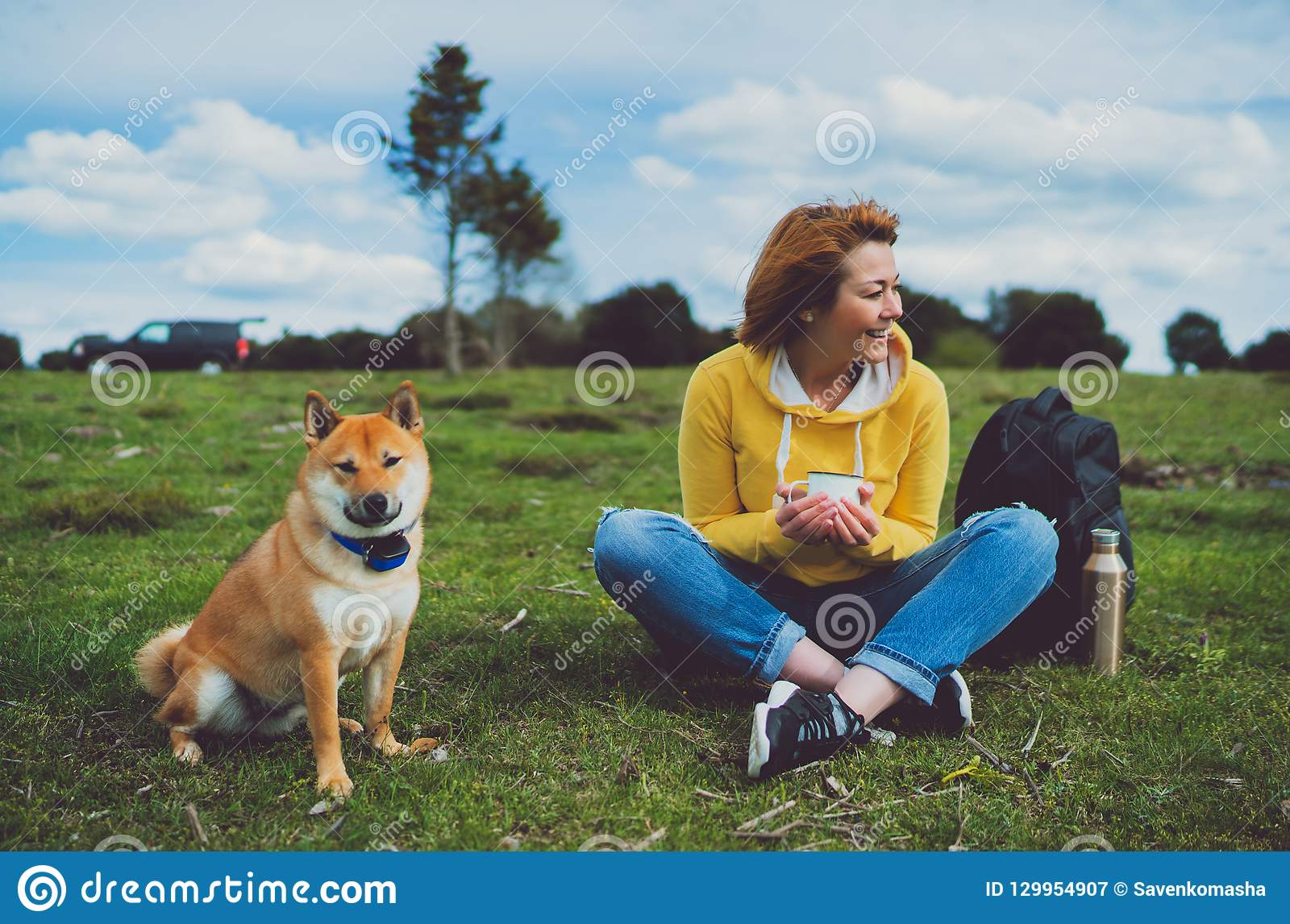 Happy smile girl holding in hands cup drink, red japanese dog shiba inu on green grass in outdoors nature park