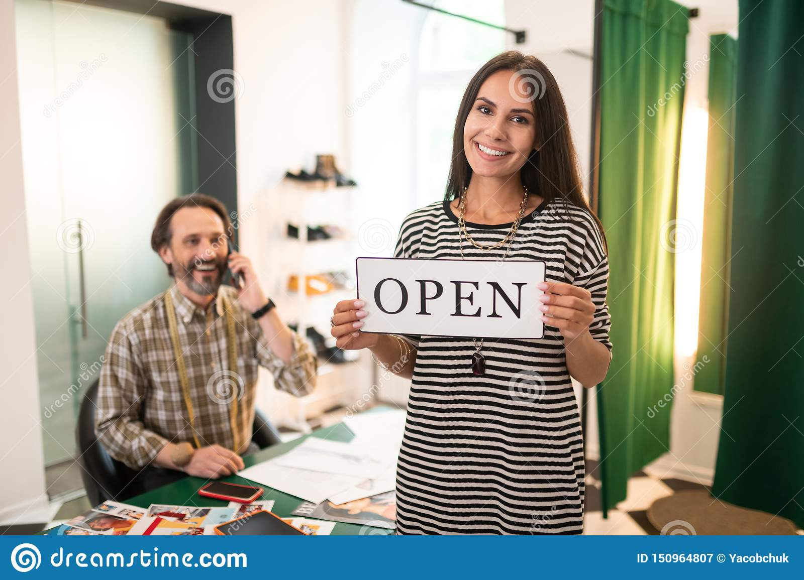 Happy smiling alluring radiant woman holding an open sign