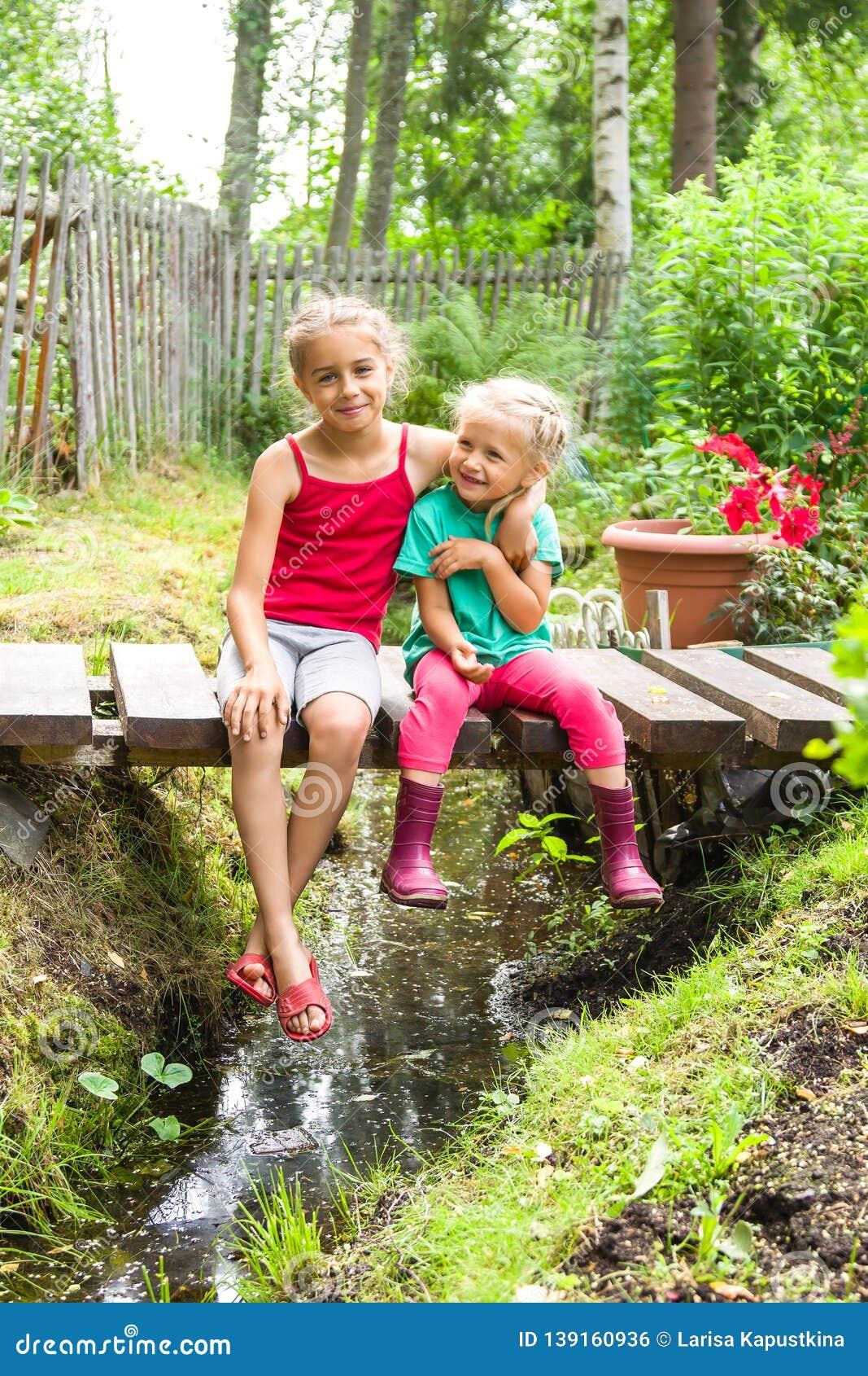 Happy Smiling Children Sitting On The Bridge At The Creek ...