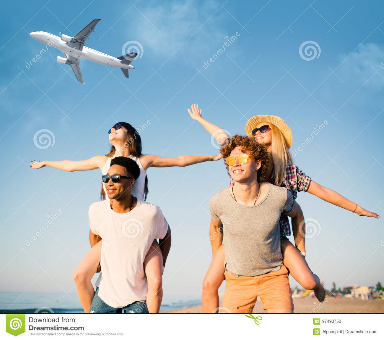 Happy smiling couples playing at the beach with aircraft in the sky