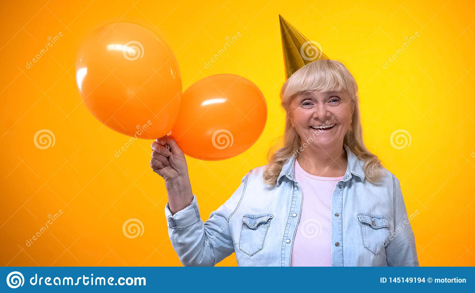 Happy smiling elderly lady holding balloons on yellow background, anniversary