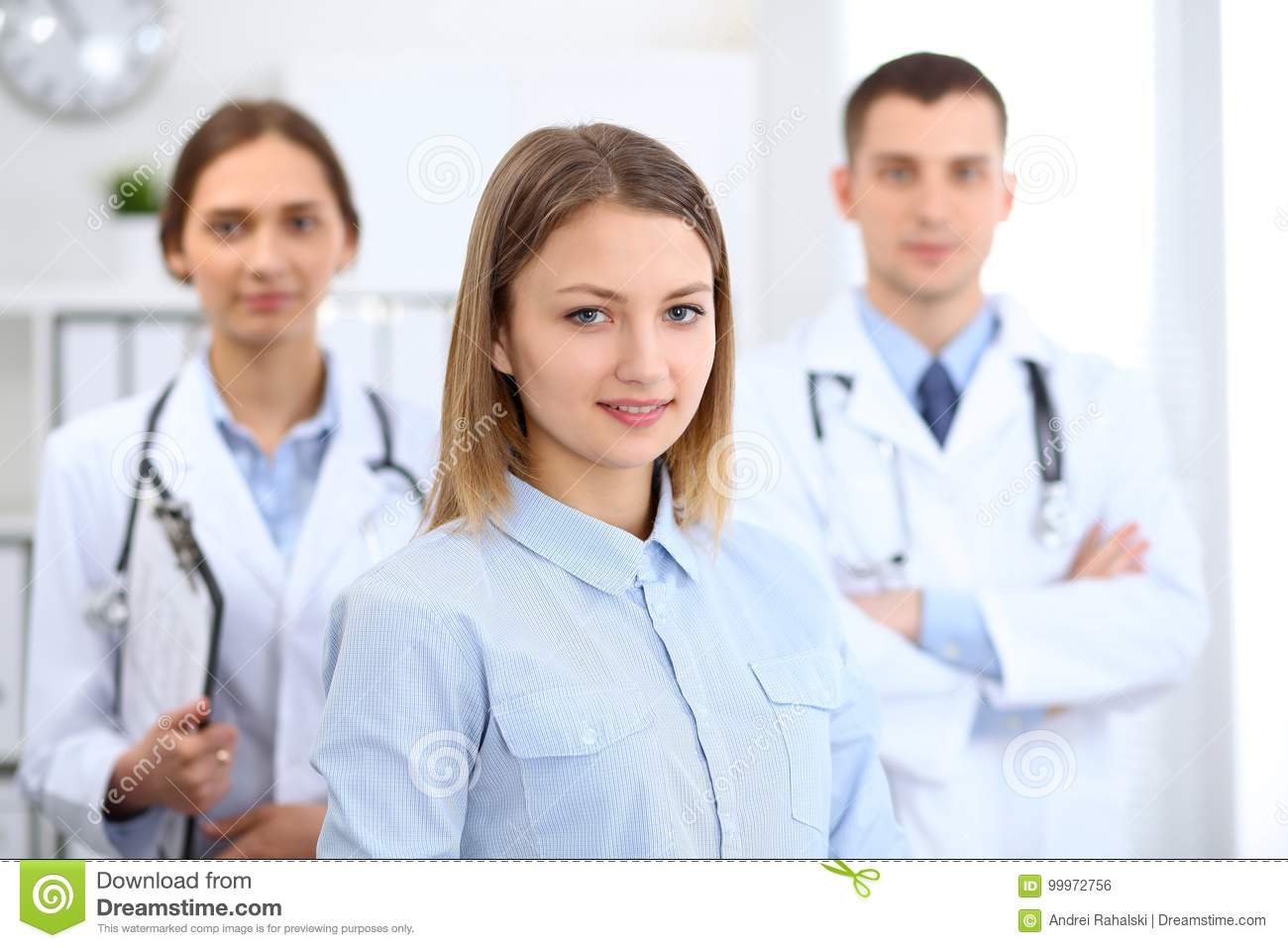 Happy smiling female patient with two cheerful doctors in the background. Medical and health care concept