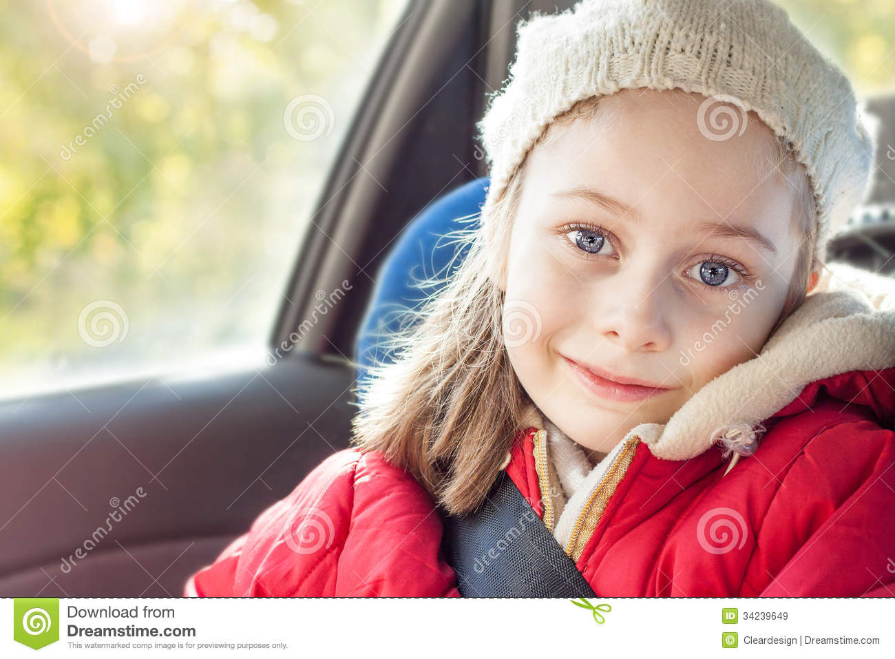 Happy Smiling Small Five Years Old Caucasian Girl In Warm Clothes Traveling A Car Seat