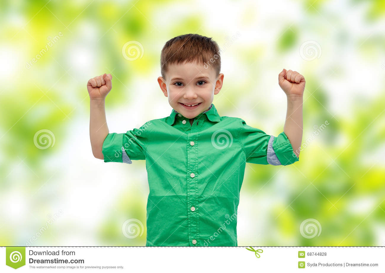 3342dcda72ff8 Childhood, power, gesture and people concept - happy smiling little boy  with raised hands showing his power over green natural background