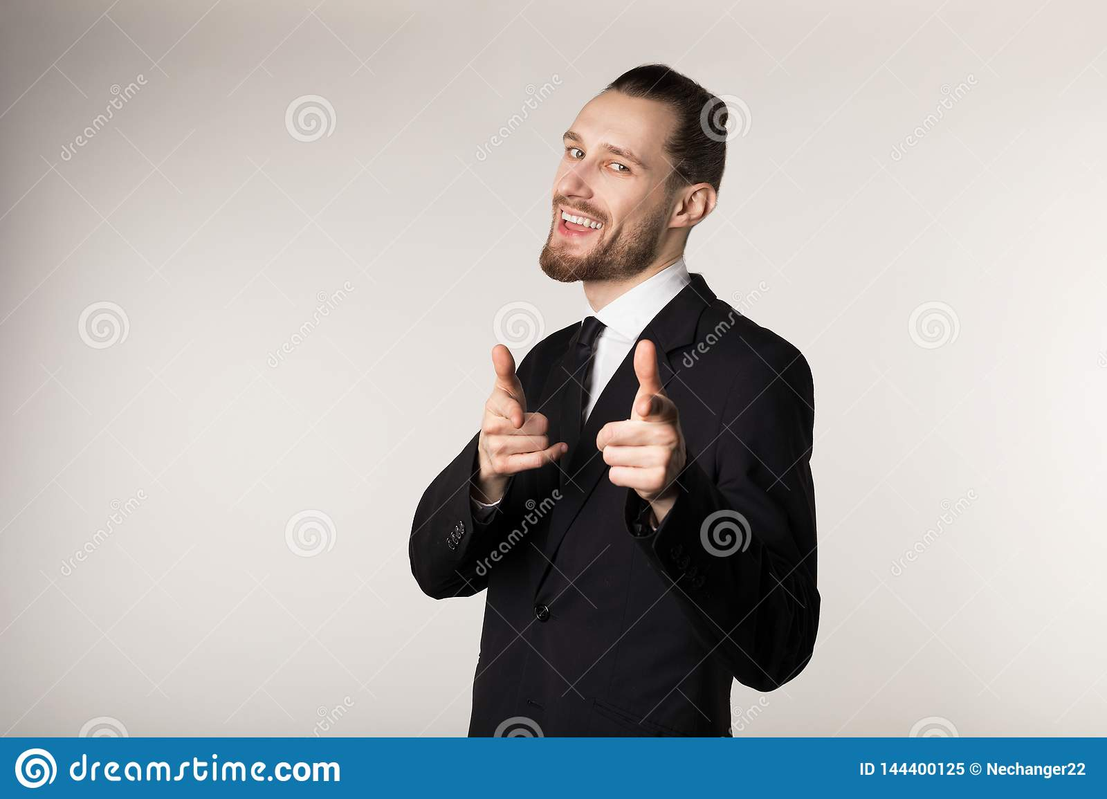 Happy smiling man with beard and trendy hairstyle wearing black suit looking and pointing at camera