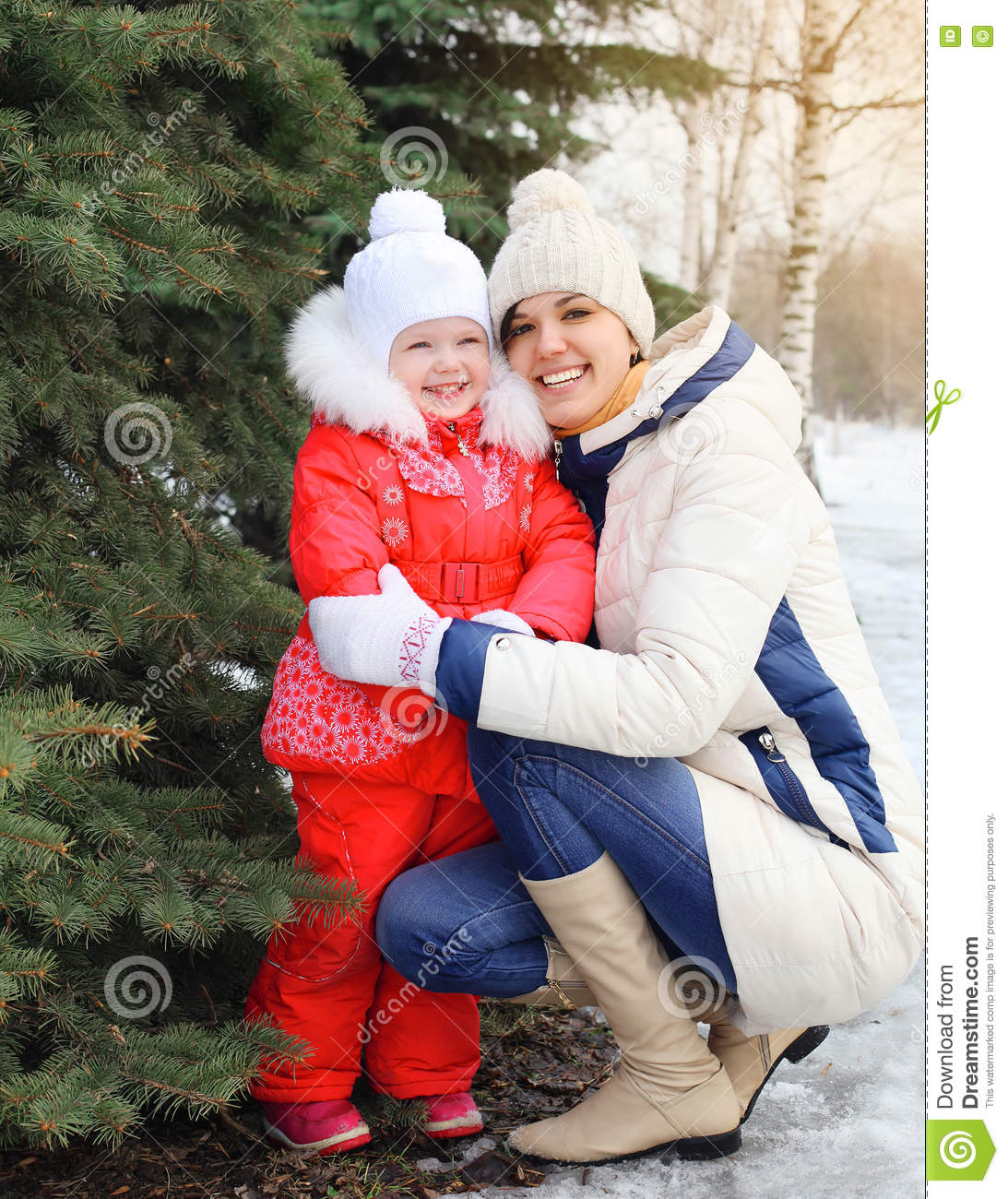 Happy smiling mother and child near christmas tree in winter