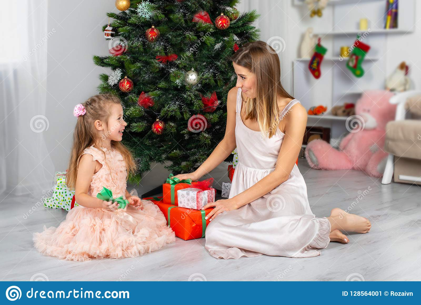 The happy and smiling mother with the daughter sit at a Christmas tree with gifts in hands
