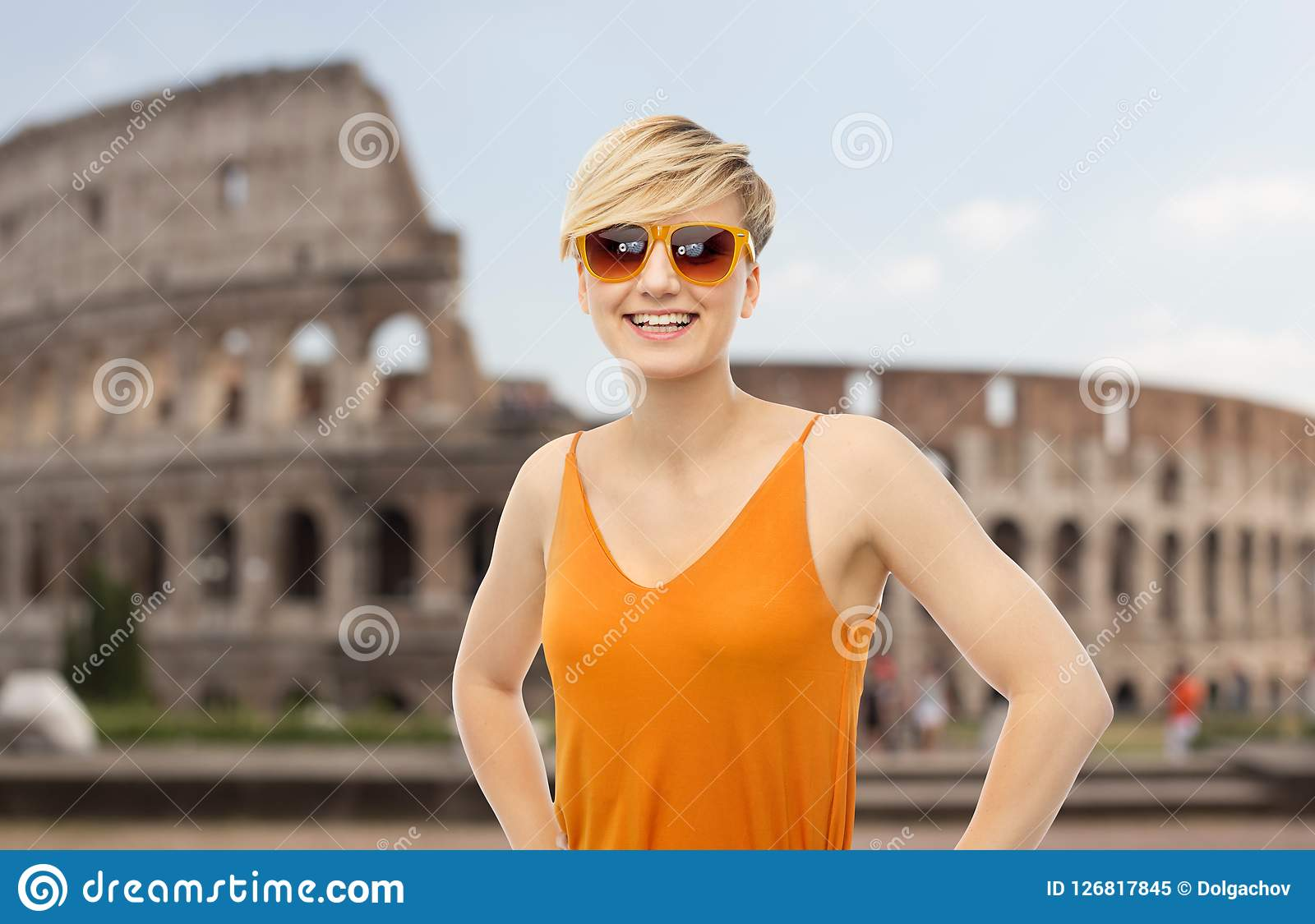 Happy smiling teenage girl over coliseum. Travel, tourism and summer holidays concept - happy smiling teenage girl in sunglasses over coliseum background Royalty Free Stock Photo