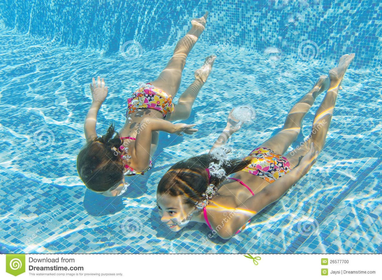 Kids Swimming Underwater happy smiling underwater children in swimming pool stock photo