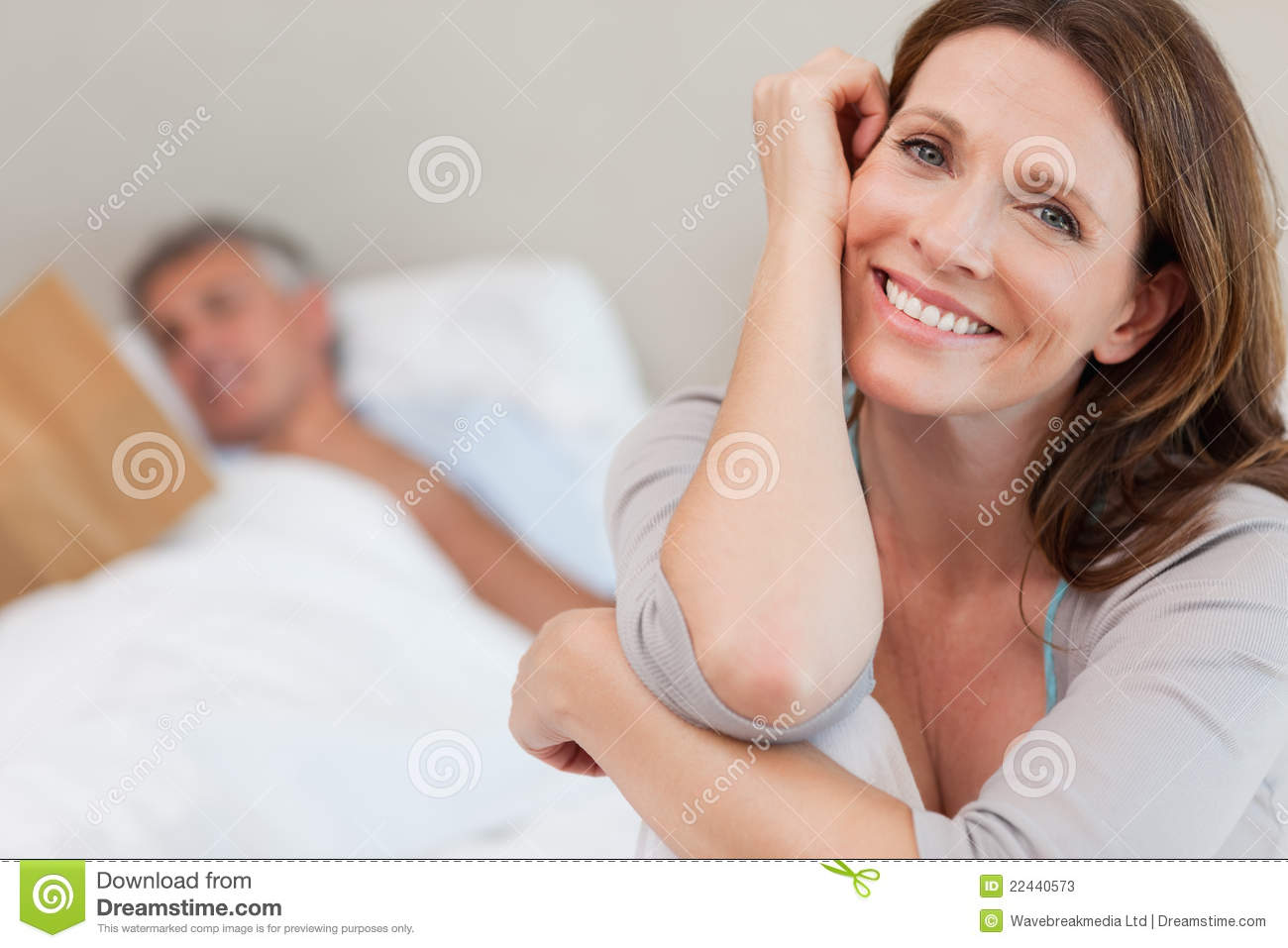 Happy smiling woman on bed with husband reading behind her