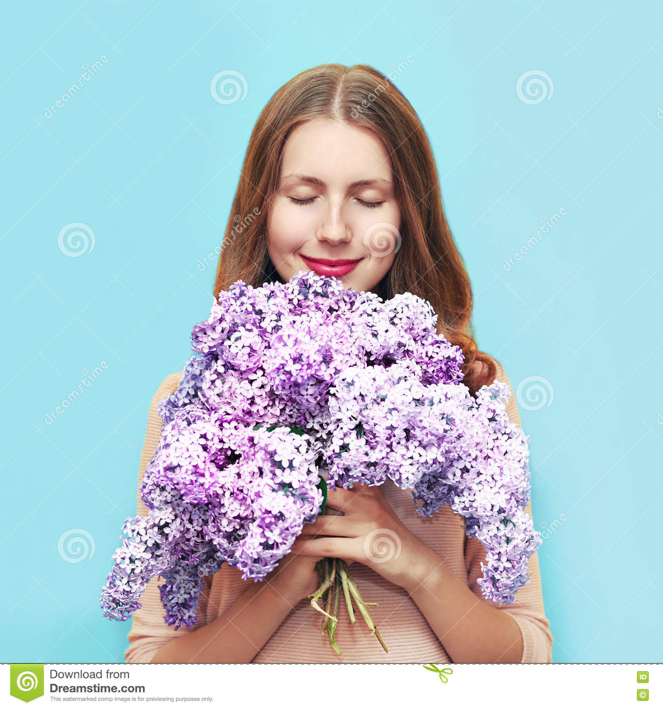 Happy smiling woman enjoying smell bouquet lilac flowers over colorful blue background
