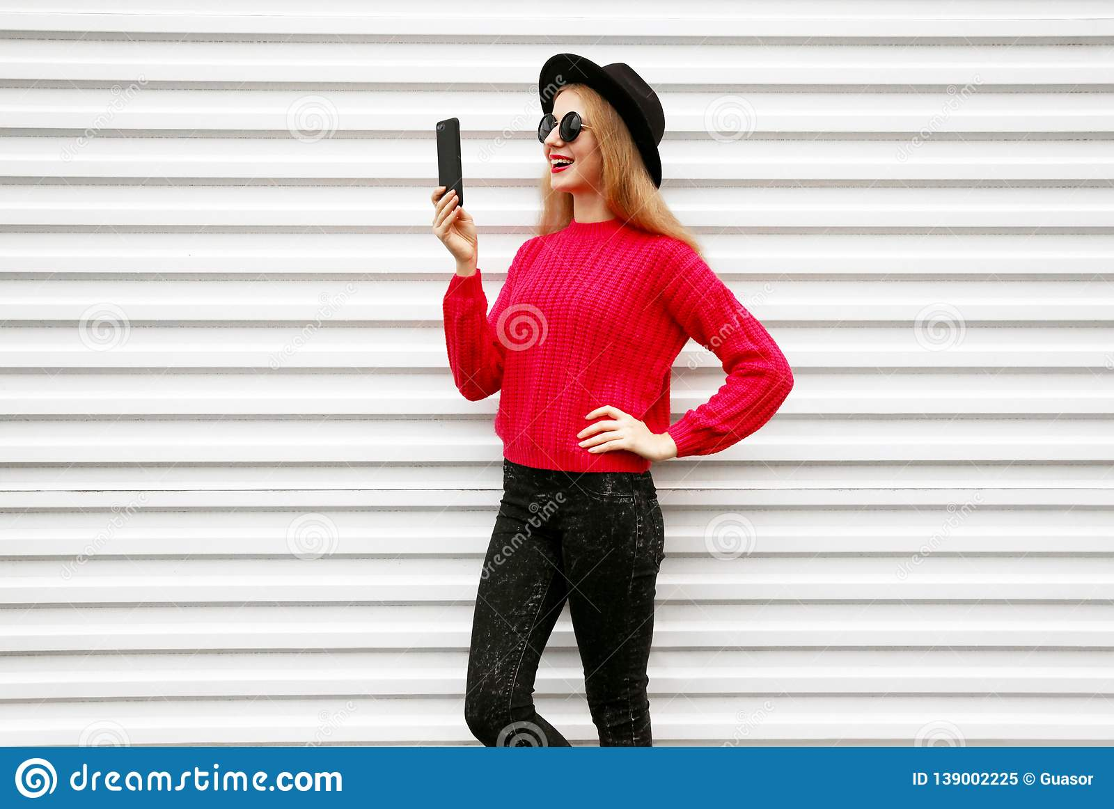 Happy smiling woman holding smartphone in colorful pink knitted sweater on city white wall