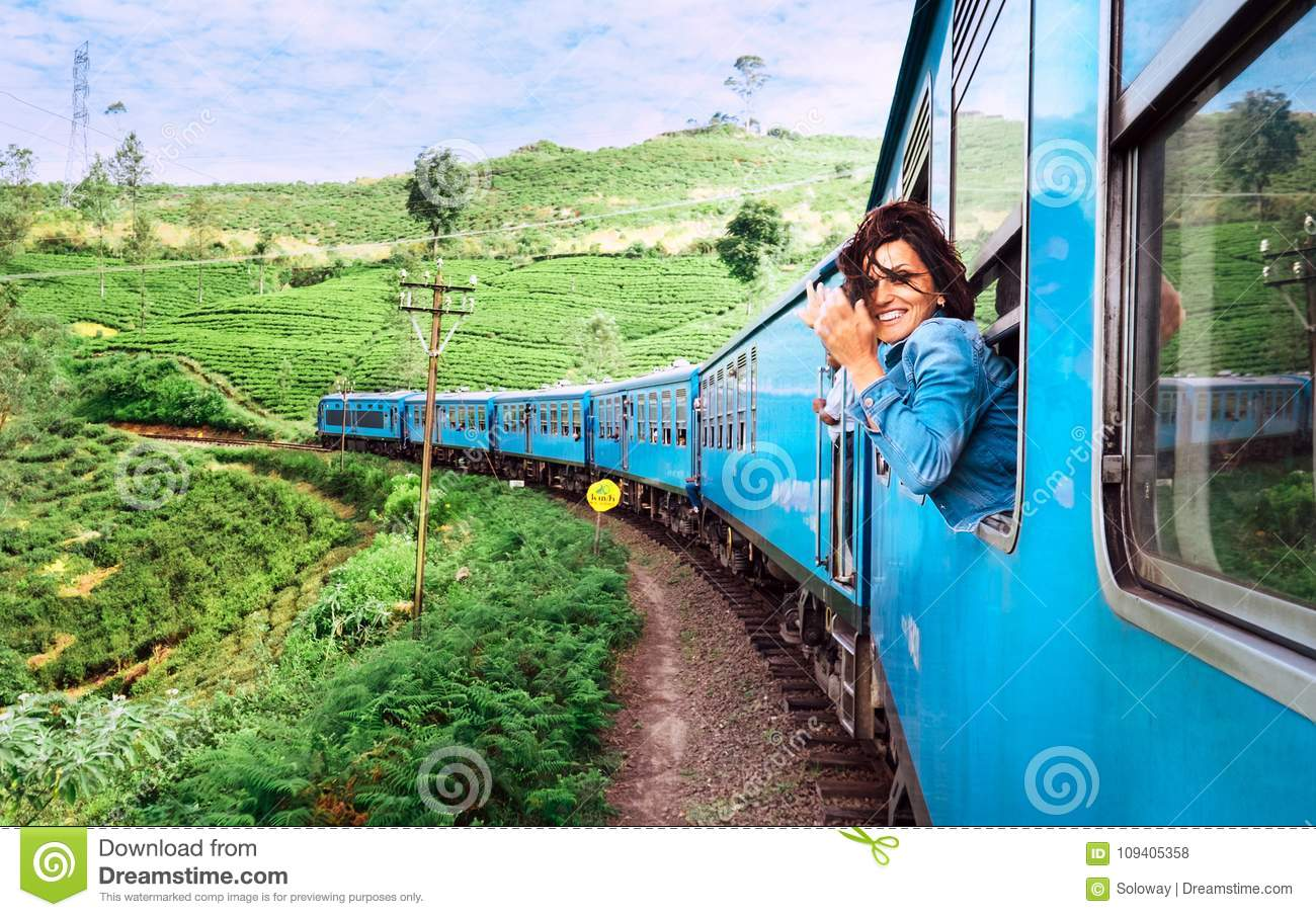 Happy smiling woman looks out from window traveling by train on