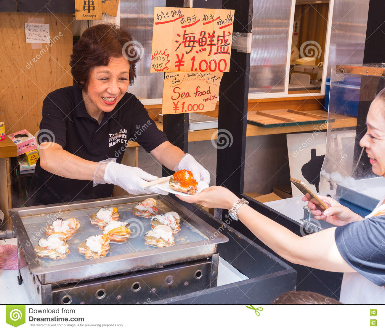 Happy smiling woman seller selling seafood dish to for Fish customer service
