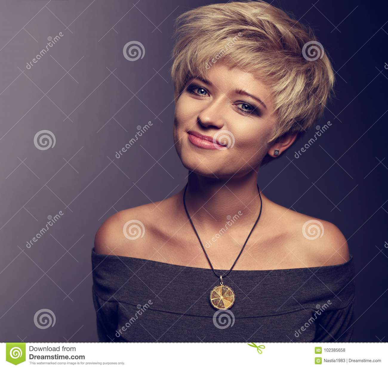 Happy smiling woman with short blond bob hairstyle in grey blous